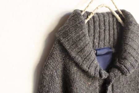 a thick knitted cardigan in brown hanging on clothes hanger on white background.Close up. Zdjęcie Seryjne