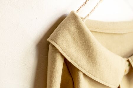 a cardigan in beige hanging on clothes hanger on white background.Close up.