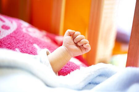 hand of an energetic newborn baby with light blue and pink blanket and baby bed. close up. Banque d'images