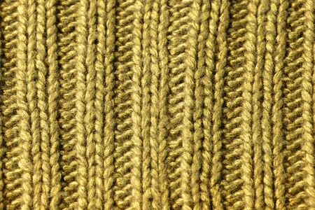 Background texture of dark yellow rib or cable stitch pattern knitted fabric made of cotton or wool. closeup. Фото со стока