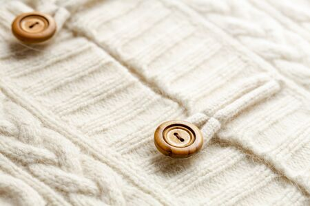Background texture of white pattern knitted fabric made of cotton or wool and wooden button. closeup. Banque d'images