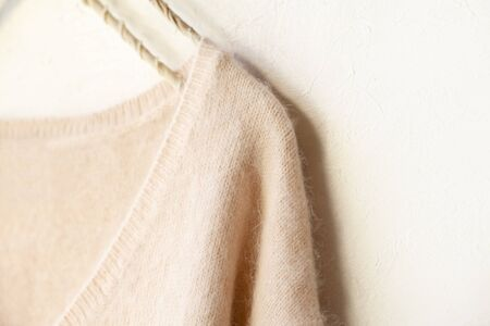 light pink sweater hanging on clothes hanger on white background.close up. Archivio Fotografico