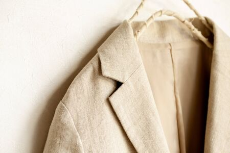 beige jacket hanging on clothes hanger on white background.close up. Stockfoto
