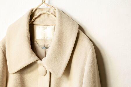beige wollen jas opknoping op kleerhanger op witte background.close up.