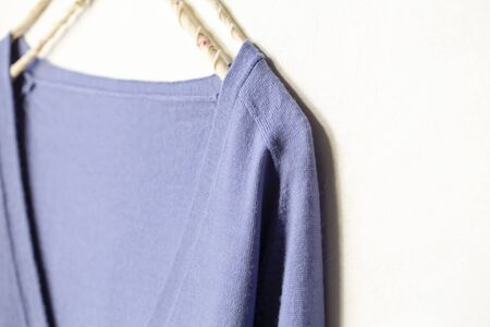 blue wool sweater hanging on clothes hanger on white background.close up.