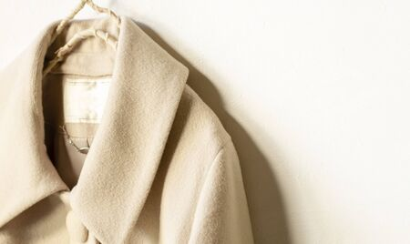 beige wool coat hanging on clothes hanger on white background.close up. Zdjęcie Seryjne