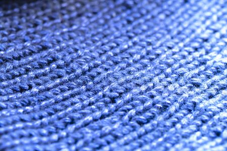 Background texture of blue pattern knitted fabric made of cotton or wool. close up.