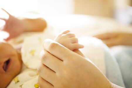 Holding Hands. hand the newborn baby in the hand of parent close up. Stock Photo