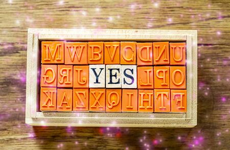 YES - isolated abstract in wood type stamps against wooden background with pink and yellow sparkle and copy space.close up.