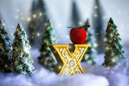 Mini snowy Christmas trees with x of the gold with apple in the forest. Bokeh lights background.close up. Stock Photo
