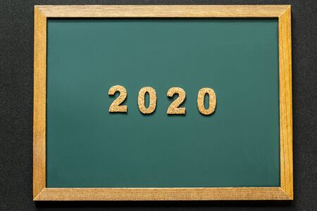 Set of 2020 of cork isolated on green blackboard and black color background and opy space. Flat lay.