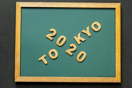 Set of 2020 TOKYO of cork isolated on green blackboard and black color background and opy space. Flat lay. Reklamní fotografie