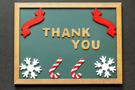 Set of THANK YOU of cork ,red ribbon, Candy Kane of the red white and two white snowy crystals isolated on green blackboard and black color background. Flat lay.