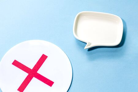 a plate of mark X and white Blank dialog speech bubble of the dish Isolated on blue Background.simple and close up.
