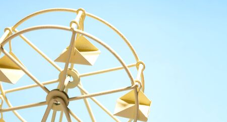 Ferris wheel of the toy on blue sky background and copy space.