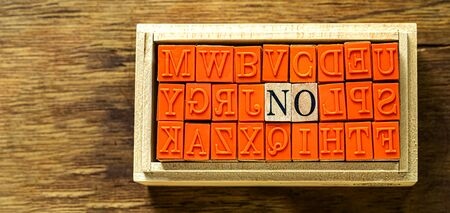 NO - isolated abstract in wood type stamps against wooden background and copy space.close up.