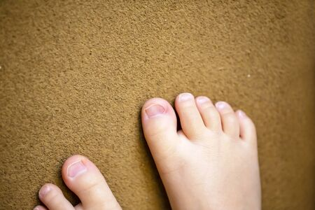 Childrens bare feet. Childs healthy bare feet on brown background.close up.