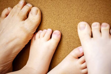 Foot of a senior and a parent and the child.Foot of three generations. grandmother,mother and child.close up.