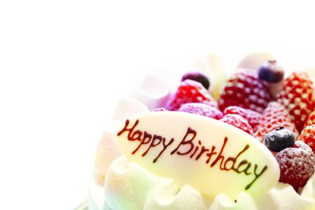 colorful and White cake decorated with strawberries and blueberries placed on a tray on a white table. Happy Birthday