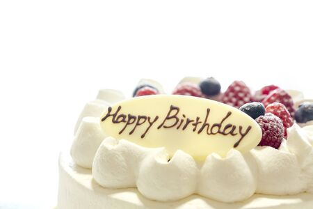 White cake decorated with strawberries and blueberries placed on a tray on a white table. Happy Birthday