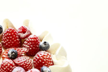 White cake decorated with strawberries and blueberries placed on a tray on a white table. close up.
