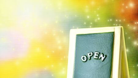 """Close up of a green with yellow """"OPEN"""" chalkboard sign leaning against sparkle ,bright with colorful background. Stock Photo"""