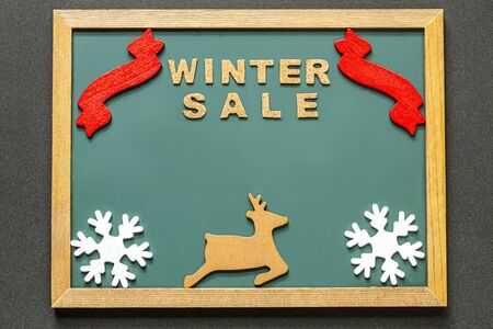 Set of WINTER SALE of cork ,red ribbon, Brown deer and two white snowy crystals isolated on green blackboard and black color background. and copy space.Flat lay.