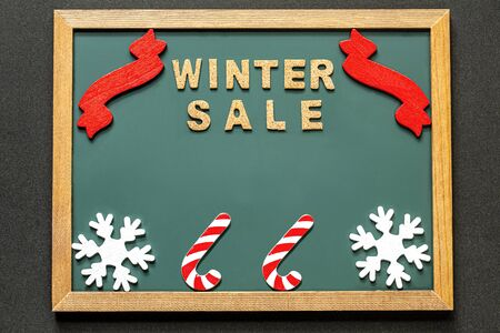 Set of WINTER SALE of cork ,red ribbon, Candy Kane of the red white and two white snowy crystals isolated on green blackboard and black color background. and copy space.Flat lay.