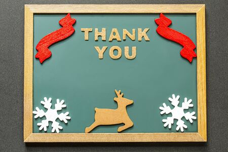 Set of THANK YOU of cork ,red ribbon, Brown deer and two white snowy crystals isolated on green blackboard and black color background. and copy space.Flat lay. Stock Photo