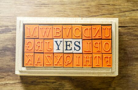 YES - isolated abstract in wood type stamps against wooden background with sparkle and copy space.close up. Stock Photo