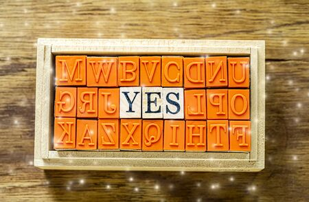 YES - isolated abstract in wood type stamps against wooden background with sparkle and copy space.close up.