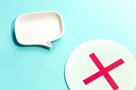 a plate of mark X and white Blank dialog speech bubble of the dish Isolated on sky blue Background.simple and close up.