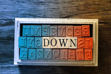 DOWN - isolated abstract in blue and orange wood type stamps against wooden background and copy space.close up.