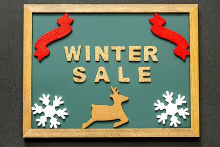 Set of WINTER SALE of cork ,red ribbon, Brown deer and two white snowy crystals isolated on green blackboard and black color background. Flat lay.