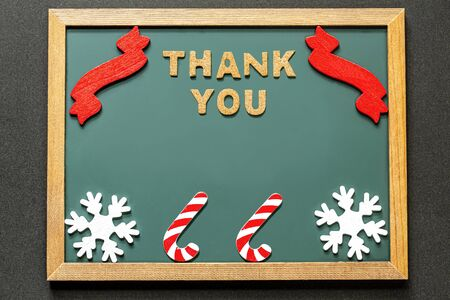 Set of THANK YOU of cork ,red ribbon, Candy Kane of the red white and two white snowy crystals isolated on green blackboard and black color background. and copy space.Flat lay.