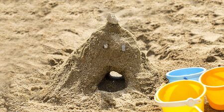 Mountain made of the sand with the face made by kids in sandbox on a playground. Blue with yellow buckets for children. 版權商用圖片