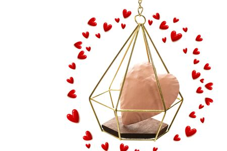 The pink heart enter the gold cage wrapped in red small hearts on white background and copy space.