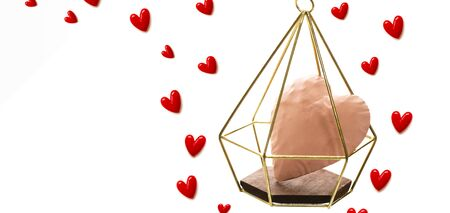 The red small hearts overflow around the pink heart enter the gold cage, and fly upwind.on white background and copy space.