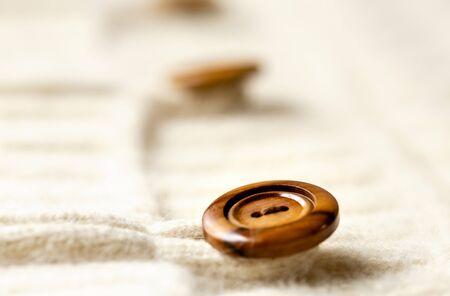 Bellissimo, lussuoso, cardigan in maglia bianca con bottone in legno. Avvicinamento.