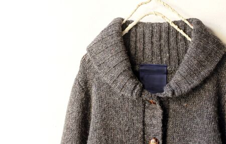 a thick knitted cardigan in brown hanging on clothes hanger on white background.Close up.