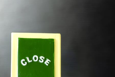 """Close up of a green ,yellow with white """"CLOSE"""" chalkboard sign leaning against bright with black background."""