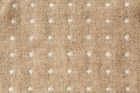 white dots in beige fabric texture useful as a background.close up and copy space. Archivio Fotografico