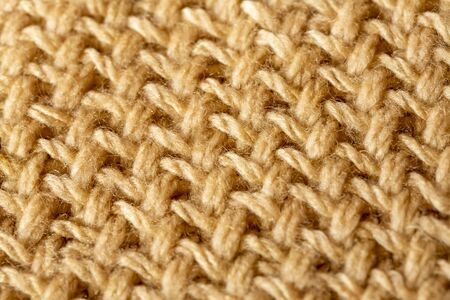 Background texture of beige pattern knitted fabric made of cotton or wool closeup Imagens