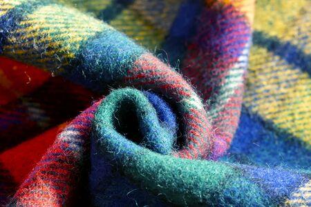 Pila di panno di lana controllato con rughe, autunno e inverno concept.close up.nero, rosso, verde, giallo, blu, bianco.