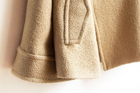 beige wool coat hanging on clothes hanger on white background.Close up. Stockfoto