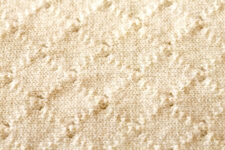 Background texture of rhombus of white pattern knitted fabric made of cotton or wool closeup