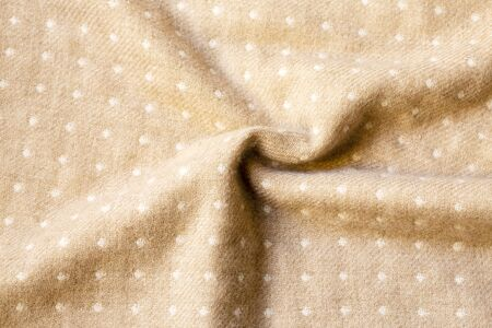 white dots in beige fabric texture and wrinkle useful as a background.close up and copy space.
