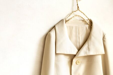 beige or white jacket hanging on clothes hanger on white background.close up.