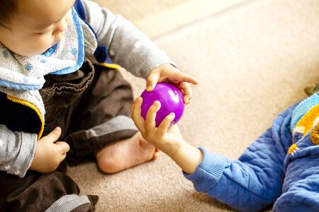 Two children play with a purple ball peacefully and copy space. Stock Photo