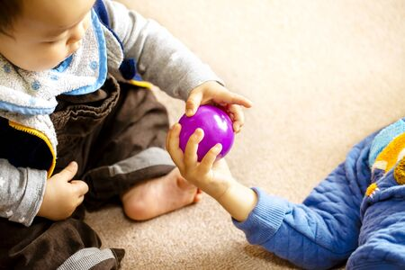Two children play with a purple ball peacefully and copy space.